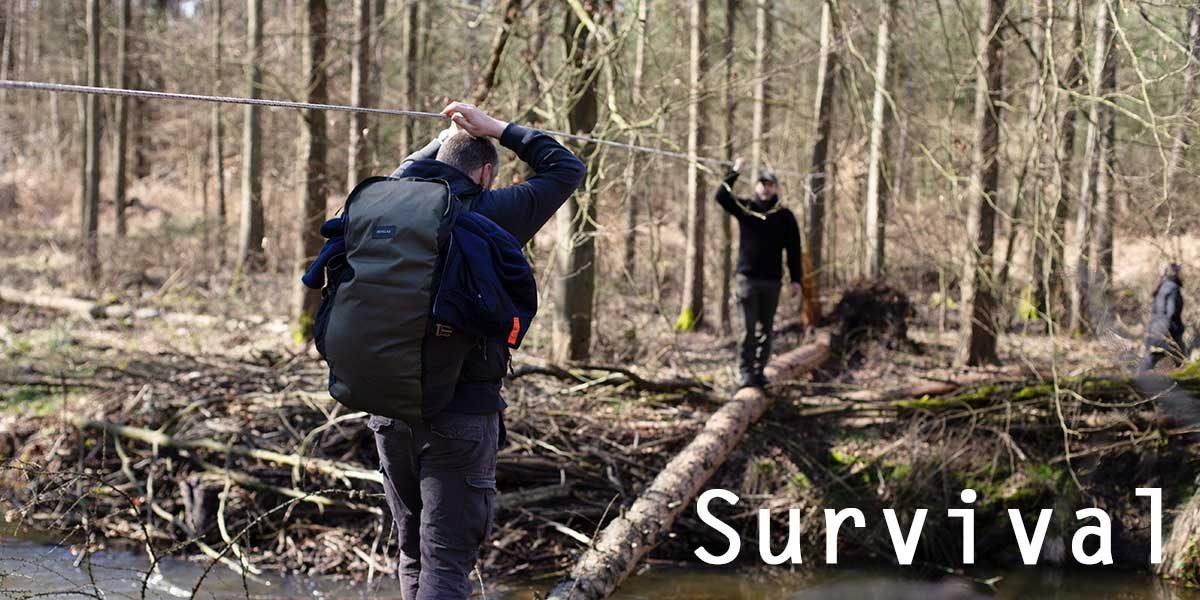 Survival Männer überqueren Baumstamm